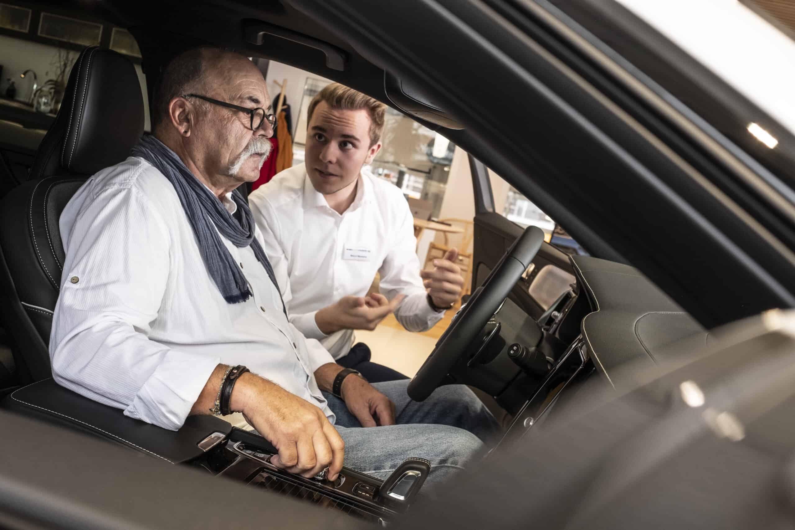 Verkäufer erklärt Kunde das Cockpit eines Autos