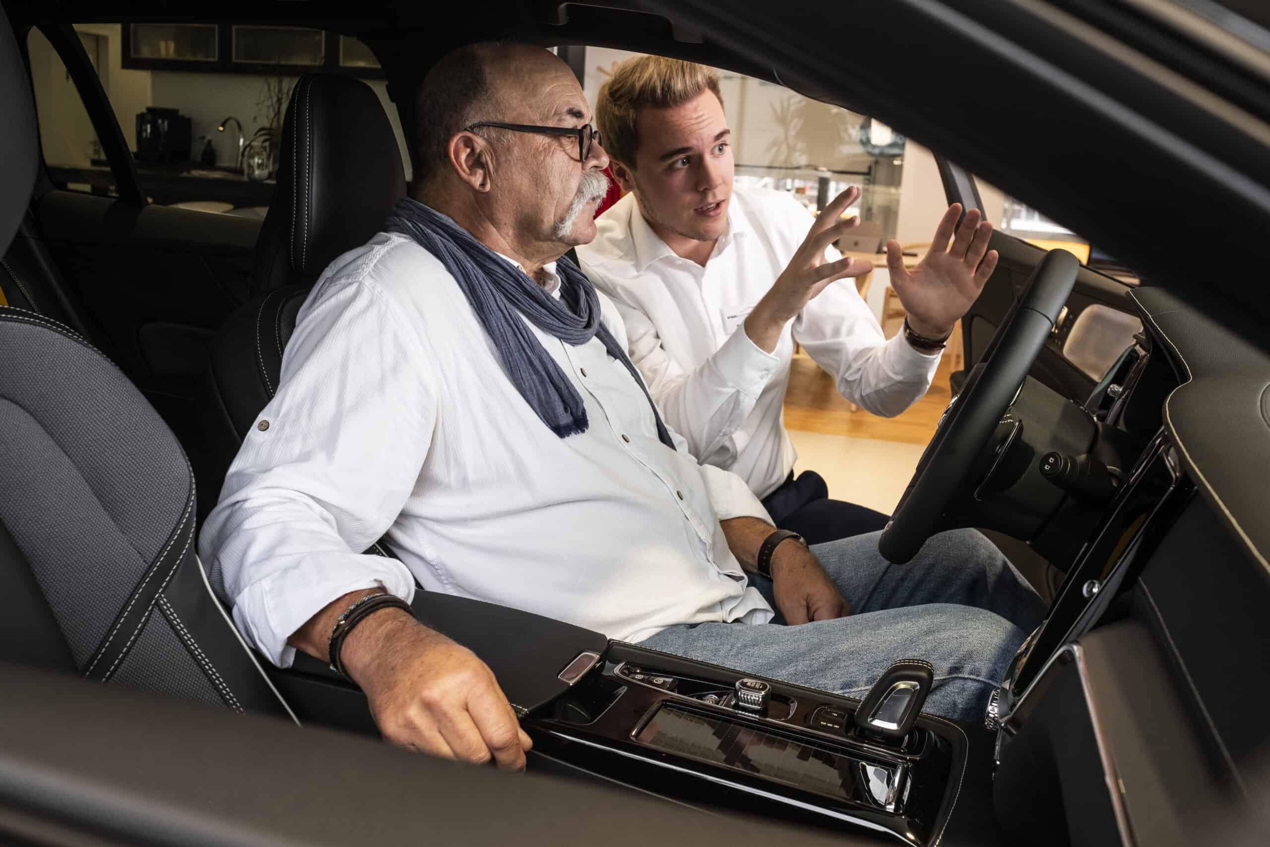 Verkäufer erklärt Kunde ein Fahrzeug