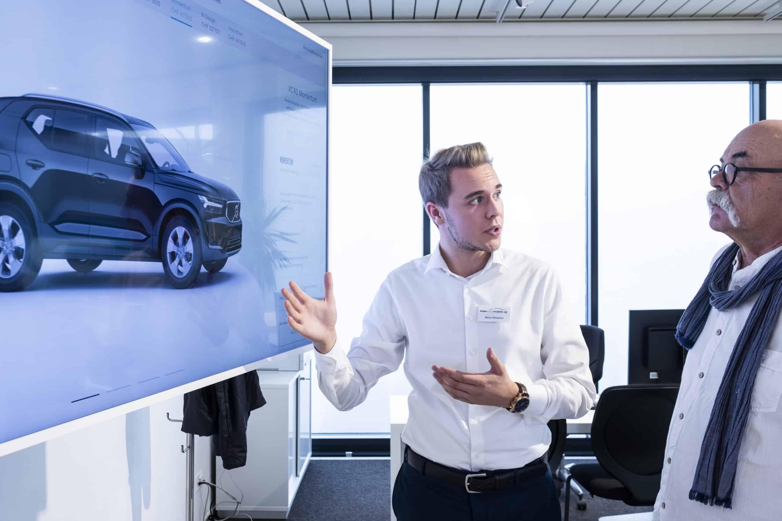Verkäufer und Kunde beim Konfigurieren eines Neuwagens